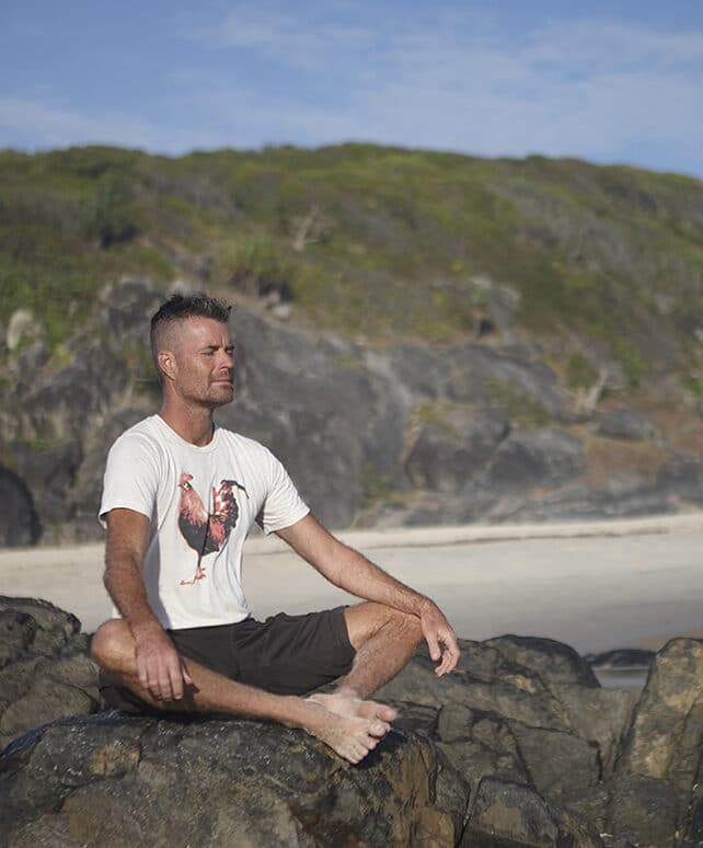 Pete Evans meditating on a beach