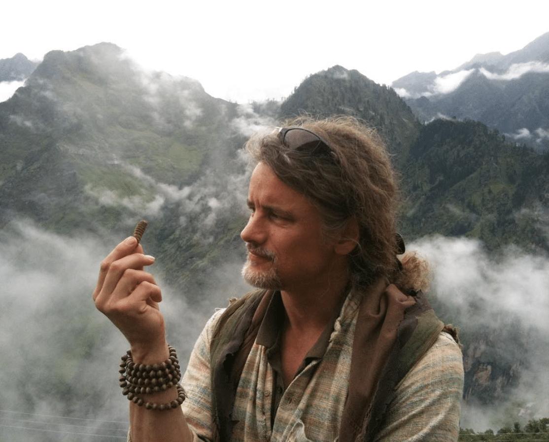 Prashanti De Jager holding a herb in the Himalayas